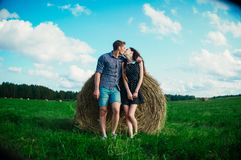 Lovers resting in a field near haystacks Stock Image