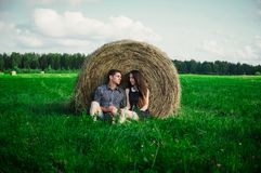 Lovers resting in a field near haystacks Royalty Free Stock Photos