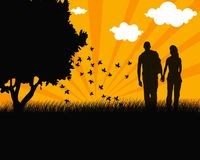 Lovers. Rnlovers walking hand in hand at sunset tree silhouette image Royalty Free Stock Image