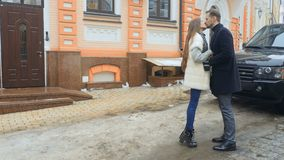 Lovers says goodbye after a date. Happy couple stands outdoors near the building. The lovers says goodbye and pretty girl with long hair kisses her boyfriend in stock video