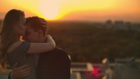 The lovers see eye to eye to each other on the roof at sunset. Romantic couple on the roof