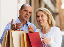 Lovers senior with mature woman having shopping tour in city. Lovers senior with mature women having shopping tour in city and smiling Royalty Free Stock Photo