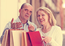 Lovers senior with mature woman having shopping tour in city. Lovers senior with mature women having shopping tour in city and smiling Stock Images
