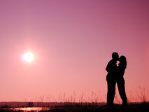 Silhouetted couple kissing. With pink sunset background Royalty Free Stock Photo