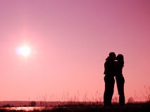 Lovers. Silhouette of lovers staying in the sun and kissing Royalty Free Stock Photography