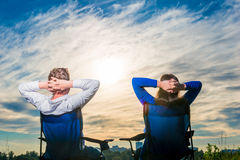 Lovers sit on the chairs and look at the beautiful  sky Royalty Free Stock Photography
