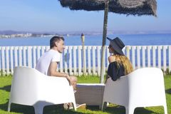 Lovers siting looking into sky and ocean, mountion, under sun umbrella. Vacation, tourism, honeymoon. Girl with a long hair stock photo