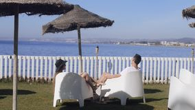 Lovers siting looking into sky and ocean, mountion, under sun umbrella. Vacation, tourism, hooneymoon. Girl with a long hair. And hat. Couple in love talks stock video footage