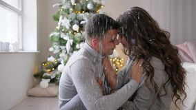 Lovers sitting on floor and hugs under artificial snow in the room near New Year tree. Lovers sitting on the floor and hugs under artificial snow in the room stock footage