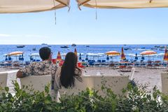 Lovers sitting, looking into sky and sea, mountion, under sun umbrella. Vacation, tourism, hooneymoon. Girl with a long hair. royalty free stock photography
