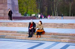Vilnius; Lithuania, 04/30/2017, Lovers sitting in a public squar. Lovers sitting in a public squar Stock Photography