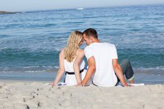 Lovers sitting on the sand Royalty Free Stock Images