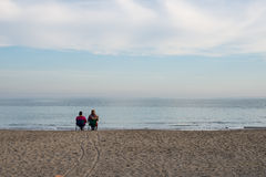Lovers sitting on the seashore royalty free stock photos