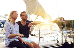 Lovers Sitting on Yacht Deck Looking Into Distance Stock Images