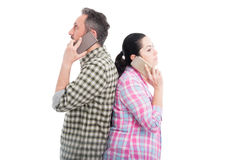 Lovers standing back to back talking on cellphones Royalty Free Stock Photo