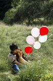 Lovers with their balloons resting in Tall Green Grass Field Royalty Free Stock Image
