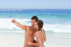 Lovers with their camera at the beach Stock Images