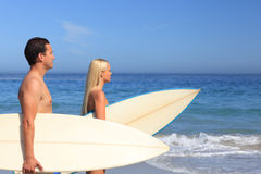 Lovers with their surfboards Stock Photos