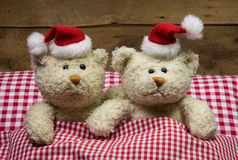 Lovers: two teddy bears sitting on christmas with hats in the be. Lovers: two teddy bears sitting on christmas with hats in the red white checkered bed Royalty Free Stock Photo