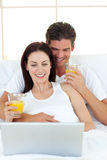 Lovers using a laptop on their bed Royalty Free Stock Image