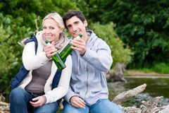 Lovers in vacation sitting at waterside clinking beer bottles Royalty Free Stock Photo