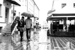 Lovers walk down the street of the old town on a rainy day . Love story stock photos