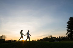 Lovers walk holding by hands. Love story. Lovers walk holding on hands. Couple in love walking at sunset. A walk in the mountains. Honeymoon. Romantic date Stock Image