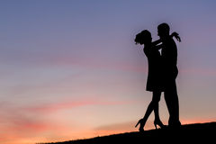 Lovers on a walk. Meeting of young people on the background of evening sky. Lovers on a walk. Silhouettes of couples in love. Happy end royalty free stock photo
