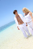 Lovers walking by the beach Stock Photos