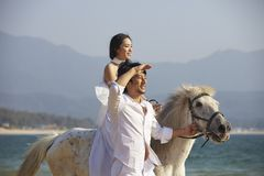 Lovers walking on beach. Chinese lovers walking on beach with horse Stock Photos