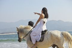 Lovers walking on beach. Chinese lovers walking on beach with horse Royalty Free Stock Photo