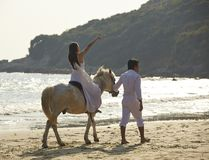 Lovers walking on beach. Chinese lovers walking on beach with horse Stock Images
