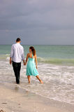 Lovers walking hand in hand along the beach in flo Royalty Free Stock Photos