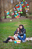 Lovers walking in the park in spring decor paper hearts Stock Image