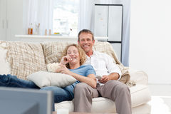 Lovers watching tv in the living room. At home Stock Images