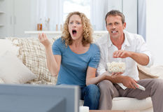 Lovers watching tv in the living room. At home Royalty Free Stock Images