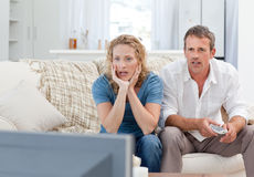 Lovers watching tv in the living room at home. During the summer Royalty Free Stock Photo