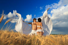 Lovers with white wings on wheat field Royalty Free Stock Images