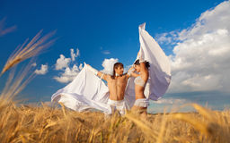 Lovers with white wings on wheat field Stock Photo