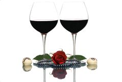 Lovers Wine. Two glasses of red wine and white truffles with a black pearl necklace and red rose between the glasses Royalty Free Stock Image
