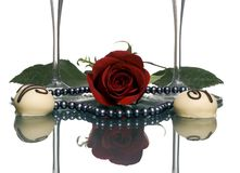 Lovers Wine 2. Two glasses of red wine and 2 white truffles with a black pearl necklace and rose between the glasses. A lovers present Stock Photo