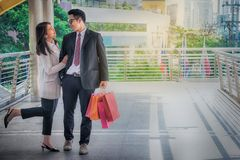 Lovers, women and men carrying many paper bags, happily shopping. On weekends stock photo