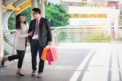 Lovers, women and men carrying many paper bags, happily shopping. On weekends stock photos