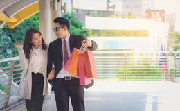 Lovers, women and men carrying many paper bags, happily shopping. On weekends royalty free stock images