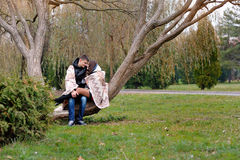 Lovers women and men walk in the park covered with a blanket Royalty Free Stock Images