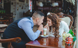 Lovers young guy and girl. The young loving couple drinks a cappuccino from one glass through tubules. Wedding Royalty Free Stock Photos