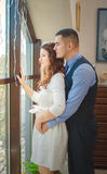 Lovers young guy and girl. The young loving couple embraces and are by the big window. Wedding Royalty Free Stock Photos
