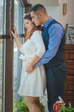 Lovers young guy and girl. The young loving couple embraces and are by the big window. Wedding Stock Image
