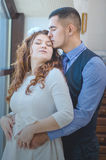 Lovers young guy and girl. The young loving couple embraces and are by the big window. Wedding Stock Photos