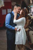 Lovers young guy and girl. The young loving couple embraces and kisses. The girl in a white dress, the men in a vest. Wedding Stock Images